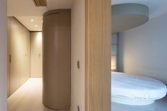 Schlafzimmer mit einem runden Bett und einer anliegenden Umkleidekabine stockbild