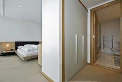 Schlafzimmer mit einem Weg in der Garderobe Stockfotografie