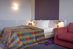 Schlafzimmer mit king-size Bett und Sofa des Leuchters Lizenzfreie Stockbilder