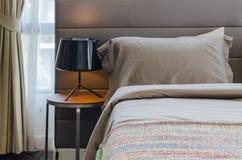 Schlafzimmer mit schwarzer Lampe auf hölzerner Tabelle Lizenzfreie Stockfotos
