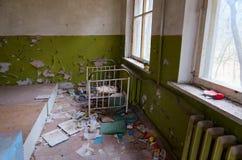 Schlafzimmer in verlassenem Kindergarten in zerstörter Dorf Kopachi-Ausschlusszone des Atomkraftwerks Tschornobyls, Ukraine lizenzfreie stockfotografie