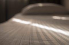 Schlafzimmerbett machte Bett suntrails stockfoto