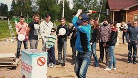 Schlag des jungen Mannes mit Kraft auf empfindlichem aufblasbarem stehen Schmiedehammer bereit Sommerfestival stock footage