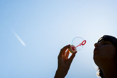 Schlagblasen der Frau gegen einen blauen Himmel Stockfotos