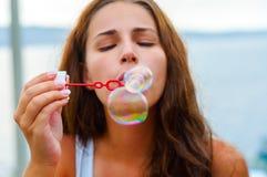 Schlagblasen der jungen Frau stockfotografie