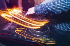 Schlagen Sie DJ mit einer Keule, das mischende Musik auf Vinyldrehscheibe spielt Lizenzfreie Stockfotografie