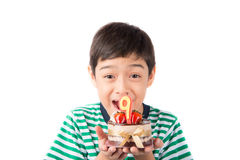 Schlagkerze des kleinen Jungen auf dem Kuchen für seinen Geburtstag Stockfoto