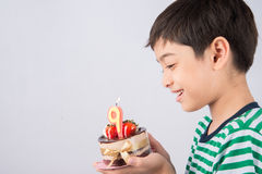 Schlagkerze des kleinen Jungen auf dem Kuchen für seinen Geburtstag Lizenzfreie Stockfotografie