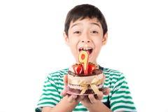 Schlagkerze des kleinen Jungen auf dem Kuchen für seinen Geburtstag Lizenzfreie Stockbilder