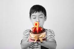 Schlagkerze des kleinen Jungen auf dem Kuchen für seinen Geburtstag Stockbild