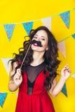 Schlagkerzen des schönen kaukasischen Mädchens auf ihr Kuchen Feier und Partei Spaß haben Junge hübsche Frau im roten Kleid und i Stockfotografie
