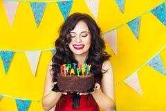 Schlagkerzen des schönen kaukasischen Mädchens auf ihr Kuchen Feier und Partei Spaß haben Junge hübsche Frau im roten Kleid und i Stockbilder
