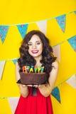 Schlagkerzen des schönen kaukasischen Mädchens auf ihr Kuchen Feier und Partei Spaß haben Junge hübsche Frau im roten Kleid und i Lizenzfreie Stockfotos