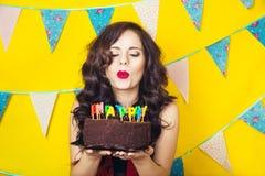Schlagkerzen des schönen kaukasischen Mädchens auf ihr Kuchen Feier und Partei Spaß haben Junge hübsche Frau im roten Kleid und i Stockfoto