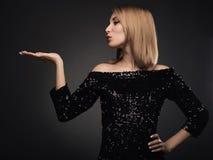 Schlagkuß der attraktiven blonden Frau gegen grauen Hintergrund lizenzfreies stockfoto
