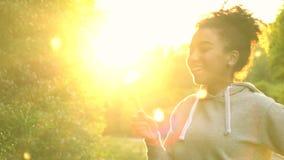 Schlaglöwenzahn der jungen Frau des Mischrasse-Afroamerikanermädchenjugendlichmädchens bei Sonnenuntergang stock video footage