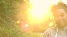 Schlaglöwenzahn der jungen Frau des Mischrasse-Afroamerikanermädchenjugendlichmädchens bei Sonnenuntergang stock footage
