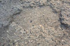 Schlagloch in Asphalt Road mit Steinen stockfotos