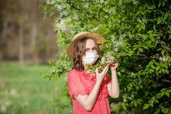 Schlagnase des jungen M?dchens und Niesen im Gewebe vor bl?hendem Baum Saisonallergene, die Leute beeinflussen Sch?ne Dame hat stockbilder