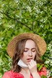 Schlagnase des jungen M?dchens und Niesen im Gewebe vor bl?hendem Baum Saisonallergene, die Leute beeinflussen Sch?ne Dame hat stockfotos