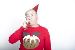 Schlagparteigebläse des älterer erwachsener Mann tragendes Weihnachtspullovers Lizenzfreies Stockfoto
