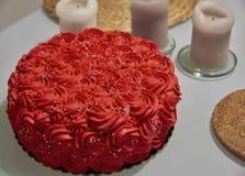 Schlagsahnekuchen des orange Rotes verziert mit silbernen essbaren Perlen und drei hohen weißen Kerzen auf weißem Hintergrund stockbild