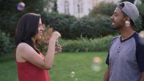 Schlagseifenblasen der Frau an ihrem Freund am Sommertag stock footage