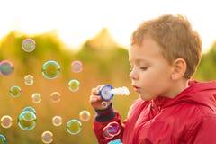 Schlagseifenblasen des kleinen Jungen draußen Stockbild