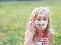 Schlagseifenblasen des kleinen Mädchens auf Frühlingswiese Stockfoto
