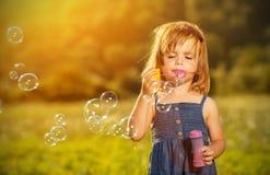 Schlagseifenblasen des kleinen Mädchens in der Natur Lizenzfreies Stockfoto