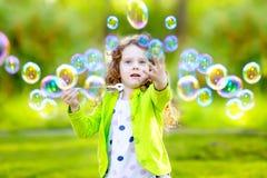 Schlagseifenblasen eines kleinen Mädchens, Nahaufnahmeporträt lizenzfreie stockfotos