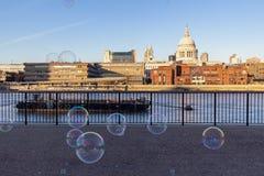 Schlagsuppenblasen des Ausführenden am schönen sonnigen Tag auf der Bank von der Themse London stockbilder