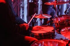 Schlagzeuger, der auf Trommelausrüstung auf Stadium spielt Nahaufnahme der Platte, Trommeln, Stöcke, in den Hintergrundszenensche Stockfotografie