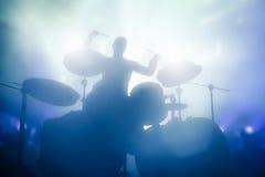 Schlagzeuger, der auf Trommeln auf Musikkonzert spielt Vereinlichter Stockbild
