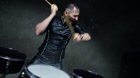Schlagzeuger, der Trommeln mit Wasser in einem dunklen Studio spielt stock video footage
