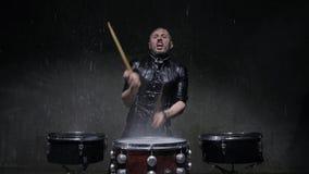 Schlagzeuger, der Trommeln mit Wasser in einem dunklen Studio spielt stock footage