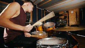 Schlagzeuger spielt leidenschaftlich Musik auf nassen Trommeln im Studio stock footage