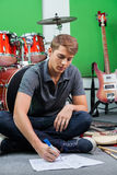 Schlagzeuger Writing Notes While, das auf Boden sitzt lizenzfreie stockfotografie