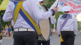 Schlagzeugerseemann mit Stöcken in seinen Händen, welche die Trommel während einer Straßenparadenahaufnahme spielen stock footage