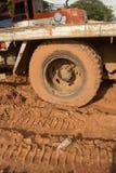 Schlamm bedeckte LKW-Reifen und -flachbett auf schlammigem Standort mit Plastikflasche Stockfotos
