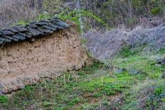 Schlammbacksteinmauer mit schwarzem Ziegeldach in der Waldfläche Stockfotos