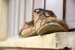 Schlammige und alte Schuhe vor dem Fenster, Arbeitskraft ` s Schuhe, Labor Lizenzfreies Stockbild