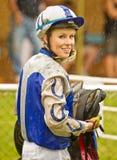 Schlammiger aber lächelnder weiblicher Jockey im Regen Lizenzfreies Stockfoto
