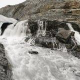 Schlammiger Fluss mit dem Wasserfall, der von unterhalb des Gletschers fließt Stockfotografie