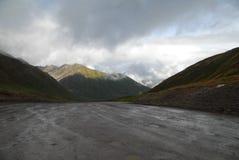 Schlammiger Schotterweg über einem Gebirgspass stockbild