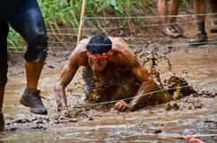 Schlammrennenteilnehmer, der durch eine Schlammgrube kriecht Stockfotografie