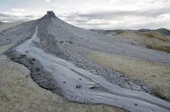 Schlammvulkaneruption im trockenen Land mit grauen Wolken im Hintergrund stockfotografie
