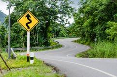 Schlange gebogene Straße und Warnzeichen Stockbild