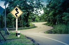 Schlange gebogene Straße und Warnzeichen Lizenzfreies Stockbild