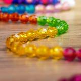 Schlange von farbigen Perlen auf einem hölzernen Hintergrund Stockbilder